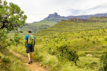 A hiking man enjoying the view to the Amphitheatre and to the rock formation Policeman's Helmet, Drakensberg mountains, Royal Natal National Park, South Africa Wall mural