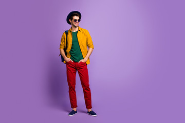 Full size photo of attractive gorgeous guy have spring walk holidays put hands in pockets wear blue bag velvet hat sunglass retro outfit isolated over purple color background