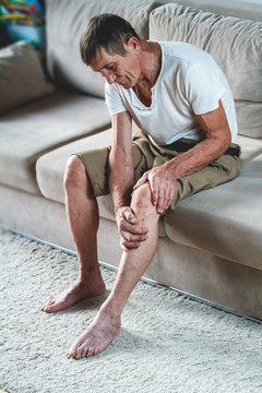 Pain in the legs and knees of an elderly senior