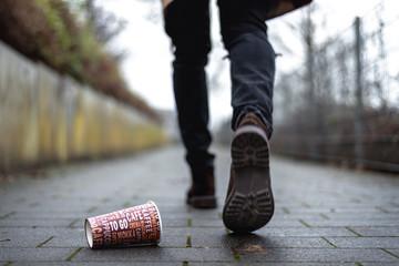 Mann wirft leeren Kaffeebecher auf Gehweg