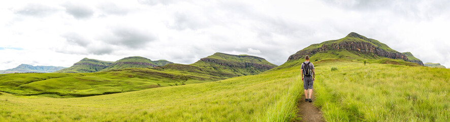 Man hiking on a small trail with a beautiful panorama of the green mountains of Maloti Drakensberg Park, Rainbow Gorge Trail, South Africa Wall mural
