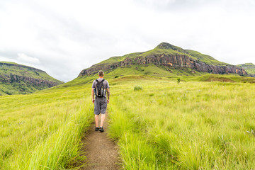 Man hiking on a small trail with a beautiful view to the green mountains of Maloti Drakensberg Park, Rainbow Gorge Trail, South Africa Wall mural