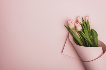 top view of tulips wrapped in paper on pink background