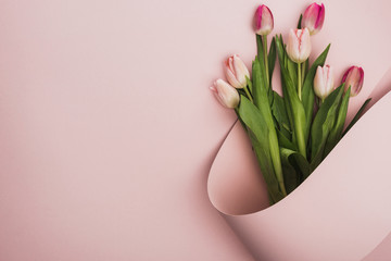top view of pink and purple tulips wrapped in paper swirl on pink background