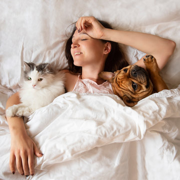 girl in bed with cat and dog