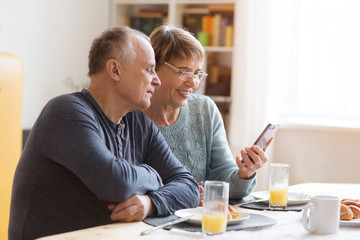 Senior couple eating breakfast and using smartphone at home