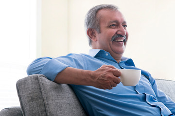 Portrait of a senior man sitting at home and drinking tea.