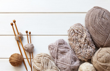 Needlework. Balls of wool yarn and wooden knitting needles on a white table. Hand knitting and craft concept. Copy space, flat lay, close up, top view