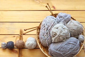 Balls of wool yarn in beige colors in a wicker basket and different types of wooden knitting needles on a wooden background. Hand knit and craft concept. Copy space, flat lay, top view