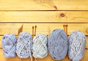 Balls of wool of different types of yarn and wooden knitting needles on a wooden background. Hand knitting and craft concept. Copy space, flat lay, close-up, top view