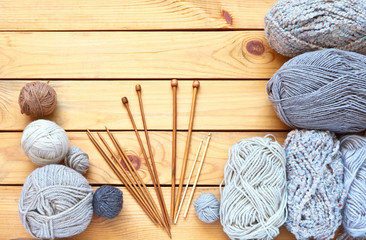 Balls of wool grey yarn and different types of wooden knitting needles and hooks on a wooden table. Hand knitting and craft concept. Copy space, flat lay, close up, top view