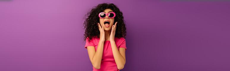 Wall Murals Hair Salon panoramic shot of scared bi-racial girl in sunglasses screaming on purple background