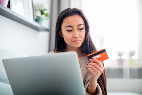 Asian girl making online payment using laptop for shopping at home