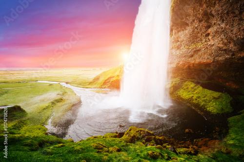 Wall mural Stunning image of powerful Seljalandsfoss waterfall in sunlight.