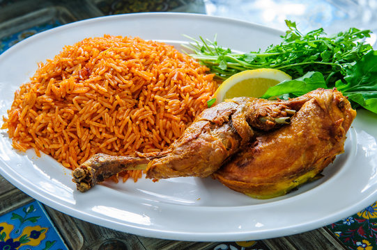 Plate of rice with duck leg and greens.