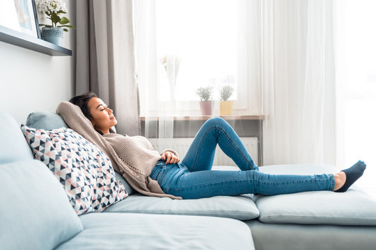 Relaxed smiling asian woman sitting on sofa at home