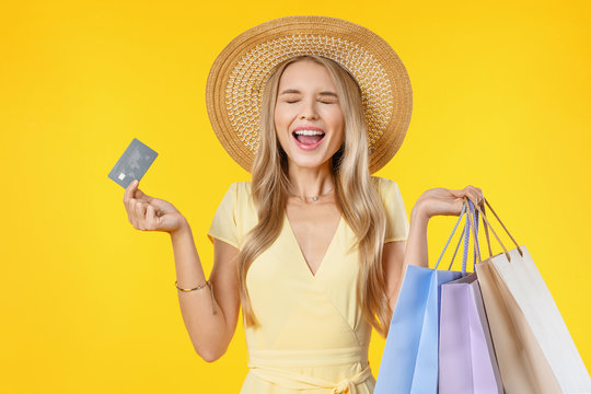 Excited screaming young woman holding shopping bags and credit card standing isolated over yellow background