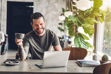 Handsome bearded hipster man use and looking at laptop computer with coffee at table in cafe.Communication and technology concept Papier Peint