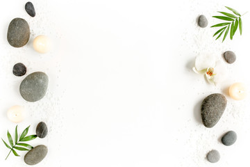 Obraz Spa stones, palm leaves, flower white orchid, candle and zen like grey stones on white background. Flat lay, top view - fototapety do salonu