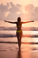 Slender female Silhouette on a background of sea waves and the sky with the setting sun