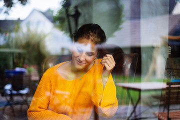 Young woman sitting laughing behind a window