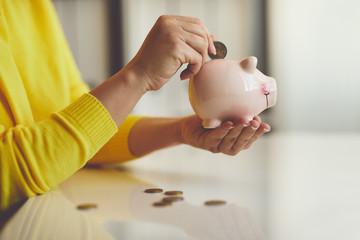 Woman puts euro coin into piggy bank