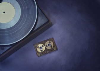 Top view of an audio cassette tape and a vinyl record, on a retro audio listening scene