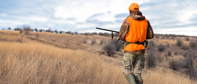 Hunter man in camouflage with a gun during the hunt in search of wild birds or game. Autumn hunting season.