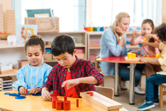 Selective focus of kids playing games with children and teacher at background in montessori school