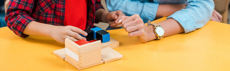 Cropped view of teacher and kid playing building blocks at desk in montessori class, panoramic shot
