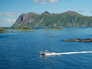 A boat leaving the famous tourist attraction Hamn Village, Senja island, Troms county - Norway