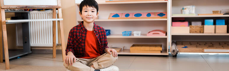 Panoramic shot of smiling asian kid sitting on floor in montessori school