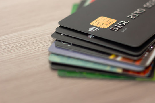 Lots of credit cards in different colors. Different credit cards. Contactless payments. The cards are on the table