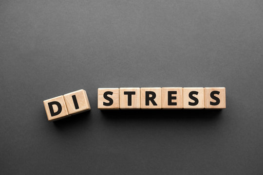 Distress Stress  - words from wooden blocks with letters, distress to stress concept, top view gray background