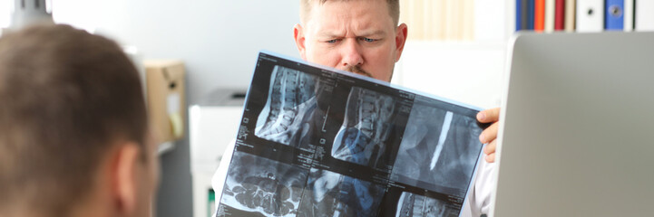 GP examining CT scan detecting problem at office workplace consulting visitor portrait