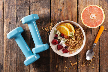 muesli, dairy and fruit- dumbbell- fitness food concept