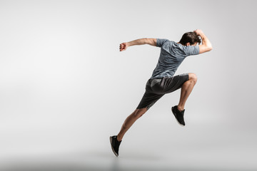Image of young athletic man doing exercise while working out