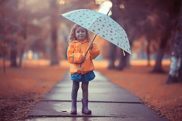 little girl with an umbrella / small child, rainy autumn walk, wet weather child with an umbrella