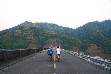 Couple tourist riding on bicycle on straight road