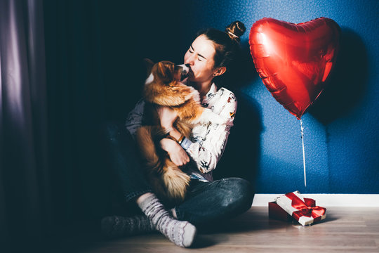 A happy girl holding a small light puppy with a red ribbon. Boyfriend giving puppy dog as valentines present to girlfriend she is happy.
