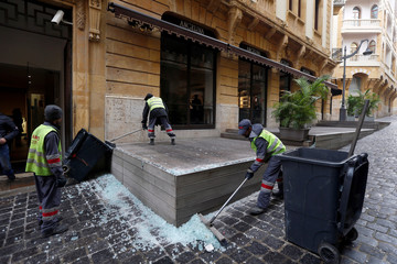 Workers clean up shattered glass from shop windows in Beirut