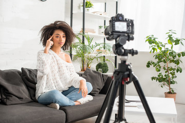 selective focus of young african american influencer sitting on sofa and pointing with finger at head near digital camera