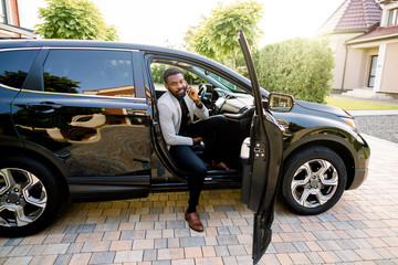 African american businessman in a suit speaking on smartphone while getting out the car