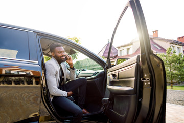Young smiling african man using smartphone while sitting on passenger seat in car. Concept of business people