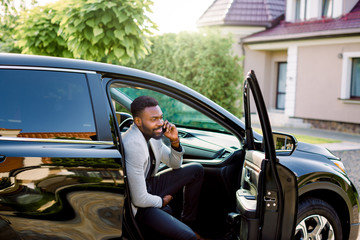 Young smiling handsome African businessman sitting in the car on passenger seat and talking on the phone. Building, house and green trees on teh background