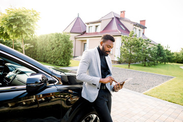 African american businessman in a suit waiting for meeting, scrolling news on gadget, or writing an email, while standing near his luxury black car crossover, outdoors, building on the background
