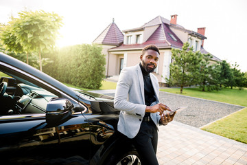 Confident African American handsome man typing e-mail on smartphone, standing near his luxury car, and looking at camera