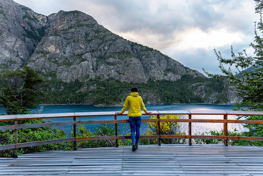 Reflection of a traveler with a yellow jacket on a viewpoint  in Bariloche, Argentina
