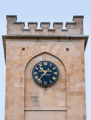 Richmond, Tasmania, Australia - December 13, 2009: Saint Luke Church. Focus on dark blue clock with golden numbers, set in top of beige stone wall of flat tower