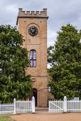 Richmond, Tasmania, Australia - December 13, 2009: Saint Luke Church. Beige stone tower with entrance and dominant clock, set between green trees with white fence, under light blue sky.